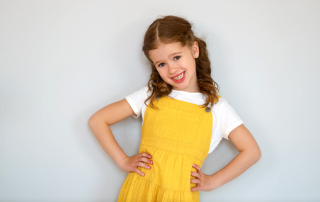 Portrait of happy cheerful child girl in yellow dress