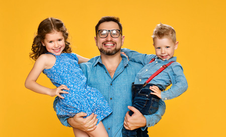 Happy fathers day! Children daughter and son congratulates dad  on yellow background