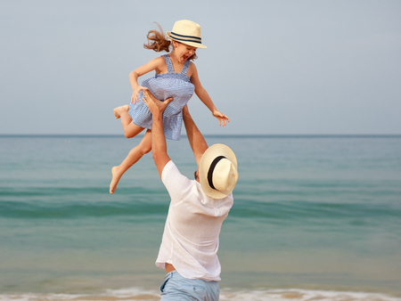 Happy family at the beach. Father and child daughter hug at sea