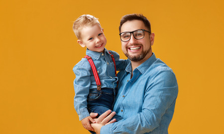 Happy fathers day! cute dad and son hugging on colored yellow background