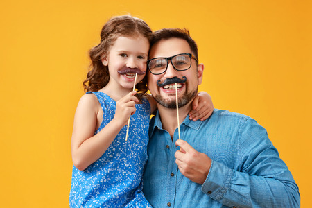 Happy fathers day! funny dad and daughter with mustache fooling around on colored yellow background Stok Fotoğraf