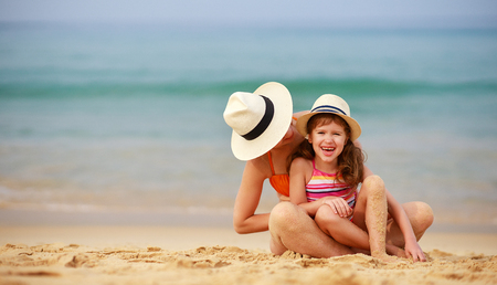 Happy family at the beach. Mother and child daughter hug at sea