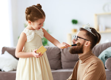 Happy fathers day! child daughter in crown does makeup to daddy and laughs Stok Fotoğraf