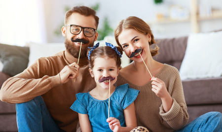 Happy funny family mother, father and child daughter with mustache on a stick