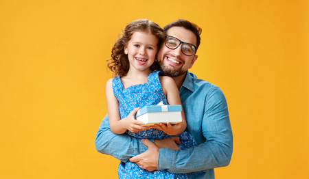 Happy fathers day! cute dad and daughter hugging on colored yellow background