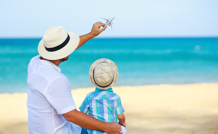 Happy fathers day! dad and child son on beach by the sea with model toy plane Stok Fotoğraf