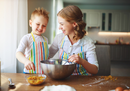 Happy family in the kitchen. Mother and child daughter preparing the dough, bake cookies Stok Fotoğraf