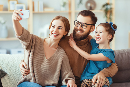 Cheerful happy family mother, father and child take selfies, take pictures at home