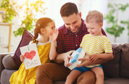 Happy fathers day! Children congratulates dad and gives him a gift and postcard