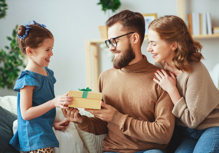 Happy fathers day! family mom and daughter congratulate dad and give a gift Stock Photo