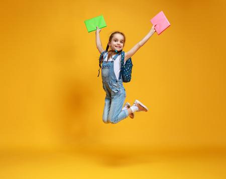 Funny child school girl on a yellow background Reklamní fotografie