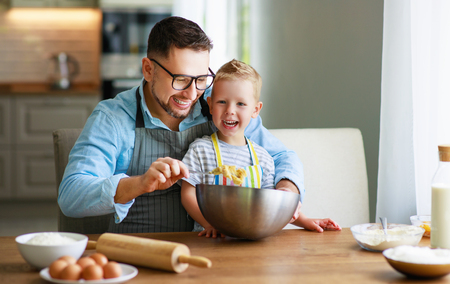 Happy family in kitchen. Father and child son baking cookies together Stockfoto