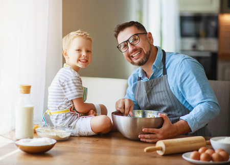 Happy family in kitchen. Father and child son baking cookies together