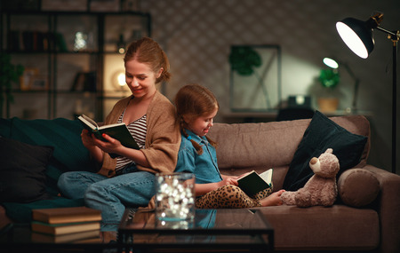 Family before going to bed mother reading to her child daughter book near a lamp in the evening Stockfoto