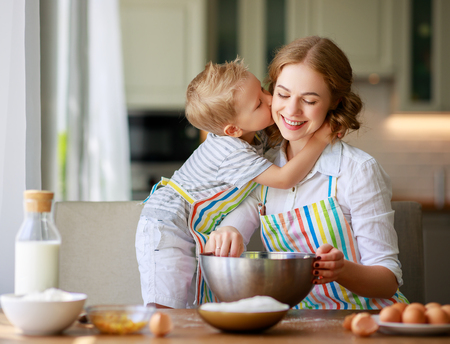 Happy family mother and child son bake kneading dough in the kitchen