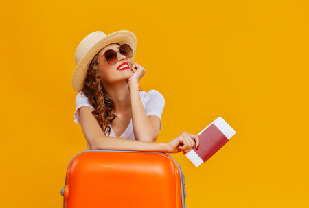 Concept of travel. Happy woman girl with suitcase and passport on yellow colored background Stock Photo