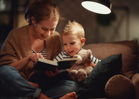 Happy family, before going to bed mother reading to her child son book near a lamp in the evening