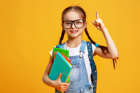 Funny child school girl on a yellow background Banque d'images - 126549492