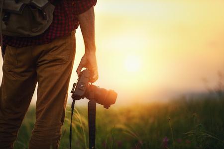 fotograf podróżniczy. człowiek podróżnik z aparatem w górach o zachodzie słońca w przyrodzie