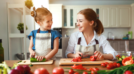 happy family mother with child girl   preparing vegetable salad at home