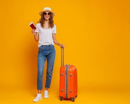 concept of travel. happy woman girl with suitcase and passport on  yellow colored background 免版税图像
