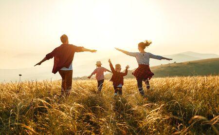 Szczęśliwa rodzina: matka, ojciec, syn i córka dzieci na przyrodzie o zachodzie słońca Zdjęcie Seryjne