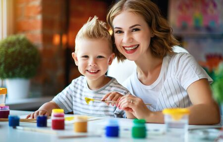 mother and child son  painting draws are engaged in creativity in kindergarten