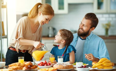 family mother father and child daughter have Breakfast in the kitchen in morning