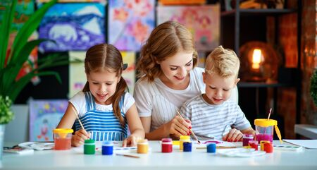 mother and children son and daughter  painting draws are engaged in creativity in kindergarten Stock Photo