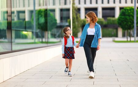 first day at school. father leads a little child girl in grade