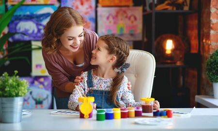 mother and child daughter painting draws are engaged in creativity in kindergarten Stock Photo - 129114973