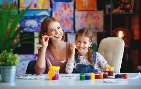 mother and child daughter painting draws are engaged in creativity in kindergarten