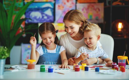 mother and children son and daughter  painting draws are engaged in creativity in kindergarten Stok Fotoğraf