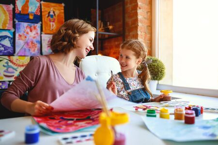 mother and child daughter painting draws are engaged in creativity in kindergarten Stock Photo - 129115383