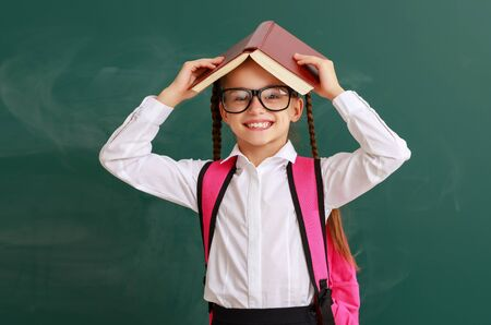 funny happy child   girl student  with book about school blackboard Stok Fotoğraf