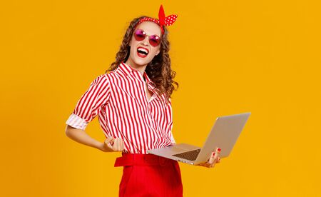 funny cheerful woman with laptop on colored yellow background