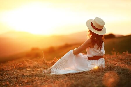 Happy woman standing with her back on the sunset in nature in summer Stok Fotoğraf