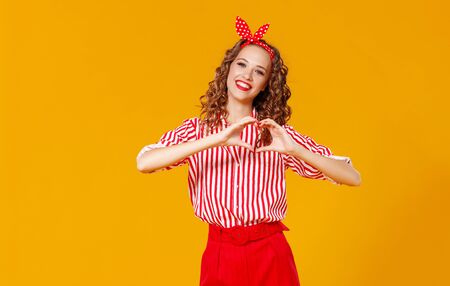 young beautiful funny girl on holds hands in shape of a heart colored yellow background