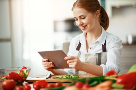 happy woman preparing vegetables in kitchen on prescription with a tablet
