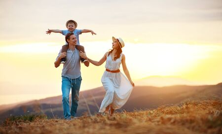 Happy family father of mother and child son  on nature at sunset