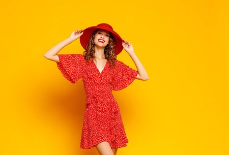 concept happy emotional young woman in red summer dress and hat jumping and laughing on yellow background Stok Fotoğraf