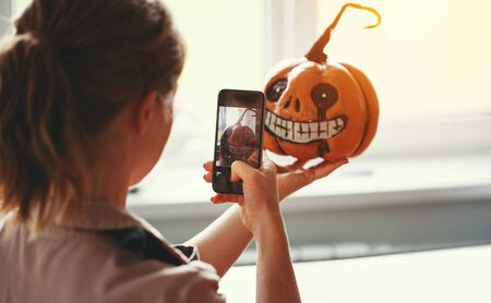 a woman artist prepares for halloween and photographed on smartphone his work painted pumpkin Stock Photo