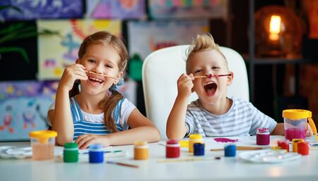 happy funny children girl  and boy draws laughing   with paint