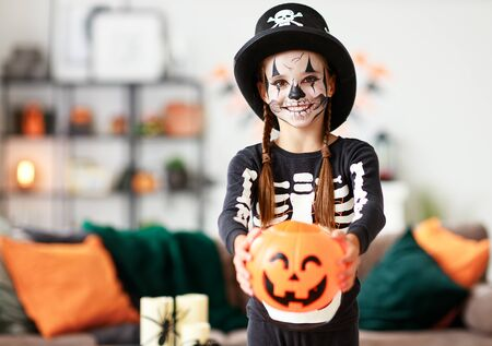 happy laughing child girl in skeleton costume to halloween