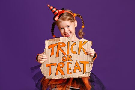 happy Halloween! cheerful child girl in costume with pumpkins on a violet purple background