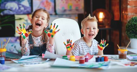 happy funny children girl  and boy draws laughing shows hands dirty with paint Stok Fotoğraf