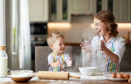 happy family in the kitchen. mother and  child son preparing the dough, bake cookies