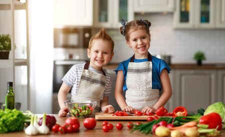 Healthy eating. Happy children prepares and eats vegetable salad in kitchen Stok Fotoğraf