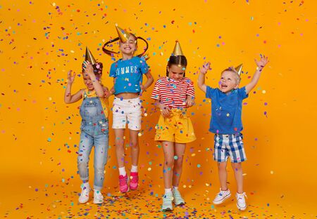 happy children on holidays have fun and  jumping in multicolored confetti on yellow background