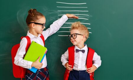 concept of progress and development in education. children boy and girl students measure growth about school blackboard